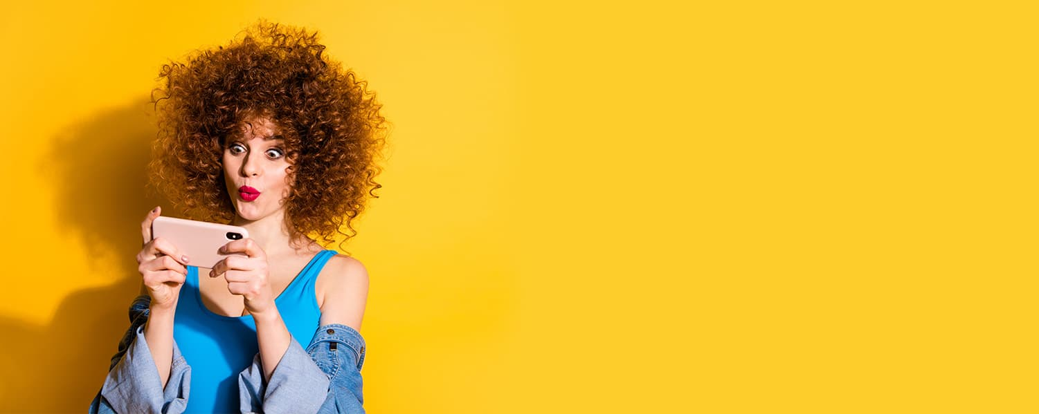 Lady looks suprised while looking at her phone, on a yellow background