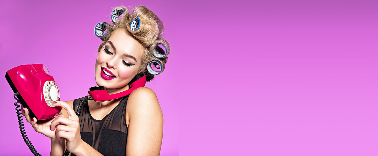 Young woman holds rotary phone to ear while dialing a number