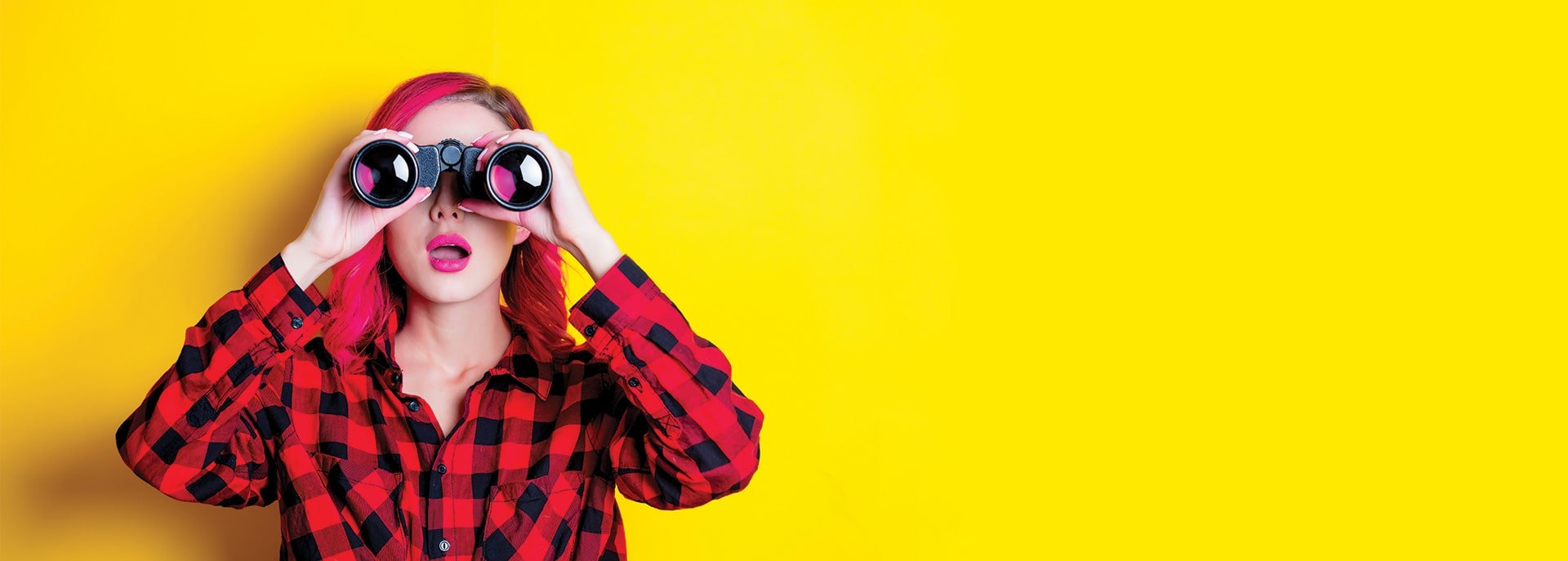 Young woman holding up Binoculars in front of a yellow background